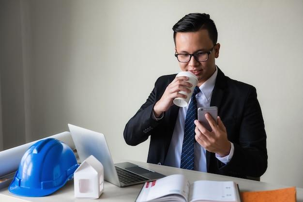 Geschäftsmann trinken kaffee und smartphone spielen Premium Fotos