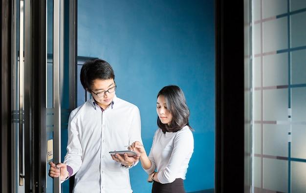Geschäftsmann und frau besprechen sich mit tablette über ihre arbeit in der halle des büros Premium Fotos