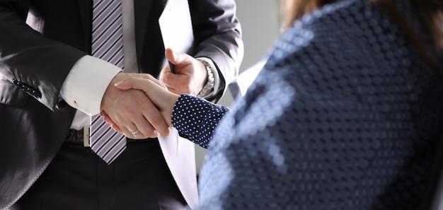 Geschäftsmann- und frauenhand rütteln innenbüro Premium Fotos
