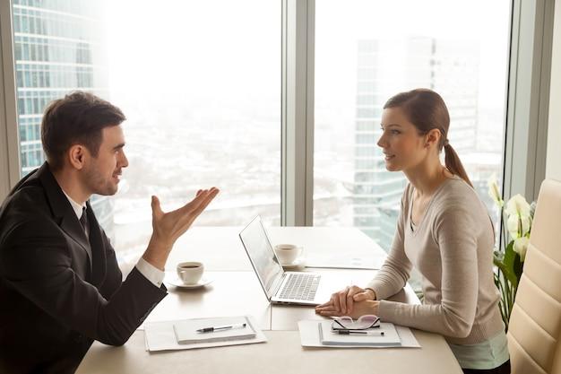 Geschäftsmann und geschäftsfrau, die arbeit am schreibtisch besprechen Kostenlose Fotos