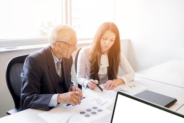Geschäftsmann und geschäftsfrau, die den unternehmensplan mit diagramm besprechen Kostenlose Fotos