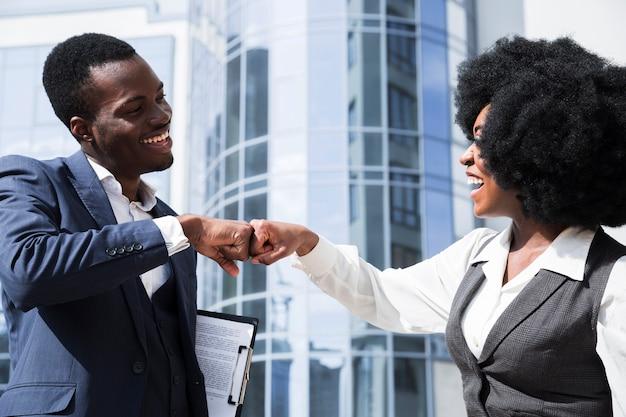 Geschäftsmann und geschäftsfrau, die ihre faust vor unternehmensgebäude stoßen Kostenlose Fotos