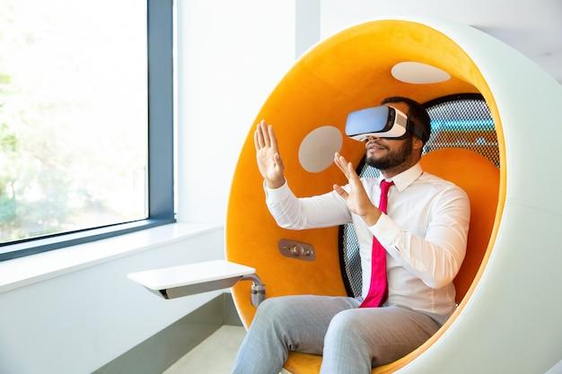 Geschäftsmann unter verwendung des kopfhörers der virtuellen realität im büro Kostenlose Fotos
