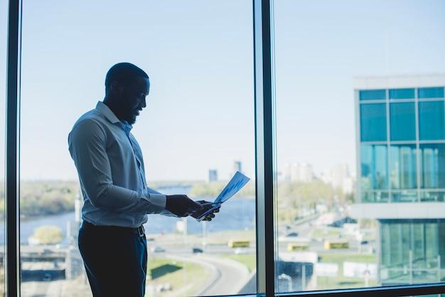 Geschäftsmann vor einem fenster mit dokument Kostenlose Fotos