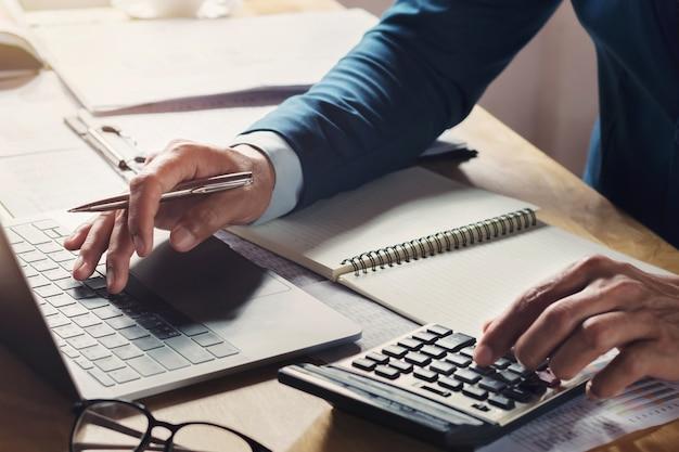 Geschäftsmann workig und mit taschenrechner mit laptop auf schreibtisch Premium Fotos