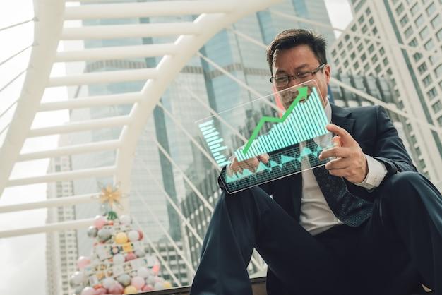 Geschäftsmann zeigt einen wachsenden virtuellen hologrammvorrat. Premium Fotos