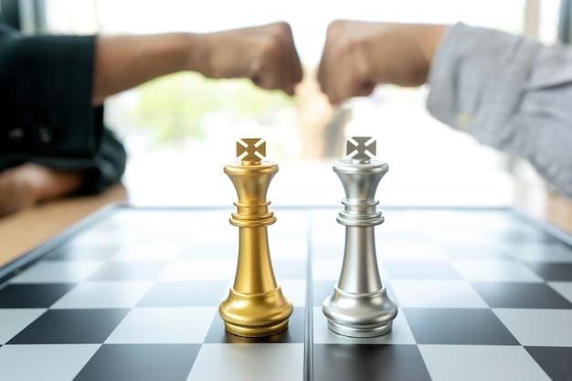 Geschäftsmannfauststoß nahe dem schachbrett mit den silbernen und goldenen schachfiguren Premium Fotos