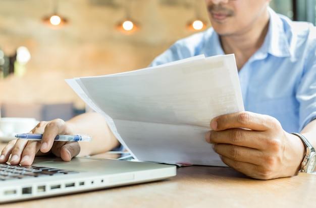 Geschäftsmannhände, die dokumentenschreibarbeit und -stift arbeiten an laptop halten. Premium Fotos