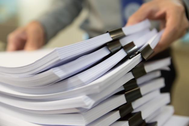 Geschäftsmannhände, die in den stapeln papierakten für das suchen von informationen über arbeitsschreibtischbüro arbeiten Premium Fotos