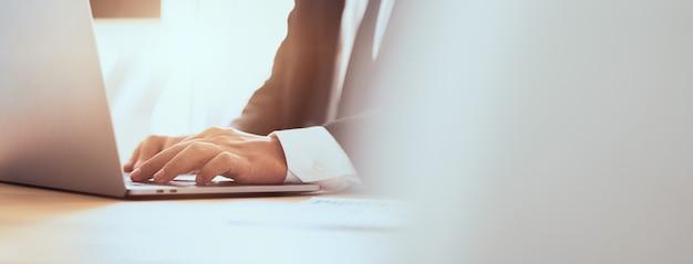 Geschäftsmannhände unter verwendung der laptop-computers mit der pressetastatur im büro. anteil des banners für anzeigen. Premium Fotos