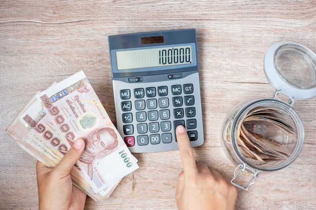 Geschäftsmannhand, die banknotenstapel des thailändischen baht hält und taschenrechner verwendet. Premium Fotos