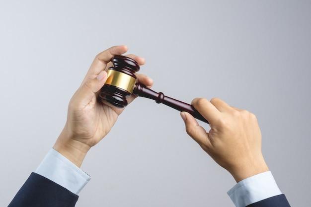 Geschäftsmannhand, die den hammer des hölzernen richters als gesetzes- oder gerechtigkeitszeichen hält Premium Fotos