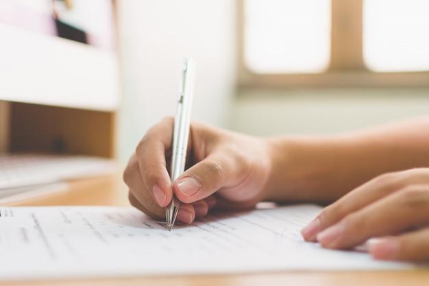 Geschäftsmannhand, die die dokumentengeschäftsvertragsvereinbarung unterzeichnet Premium Fotos