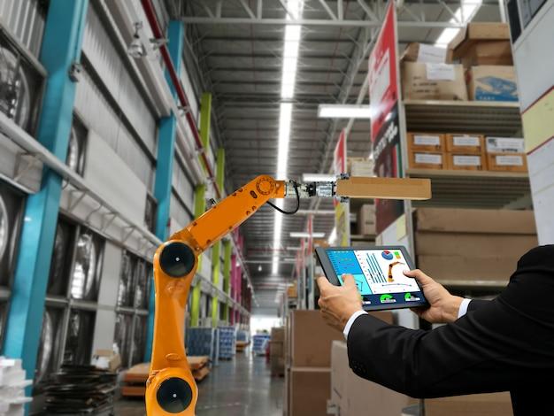 Geschäftsmannhand, die eine roboterindustrie-armproduktlagerungsfabrik und -lager der tablette intelligente hält Premium Fotos