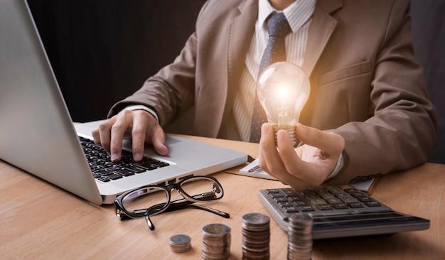 Geschäftsmannhand, die glühlampe mit der verwendung des taschenrechners hält, um zu berechnen Premium Fotos