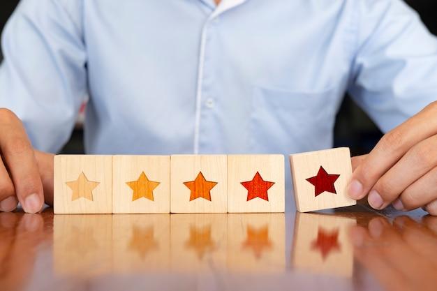 Geschäftsmannhand, die hölzerne form mit fünf sternen auf tabelle setzt. Premium Fotos