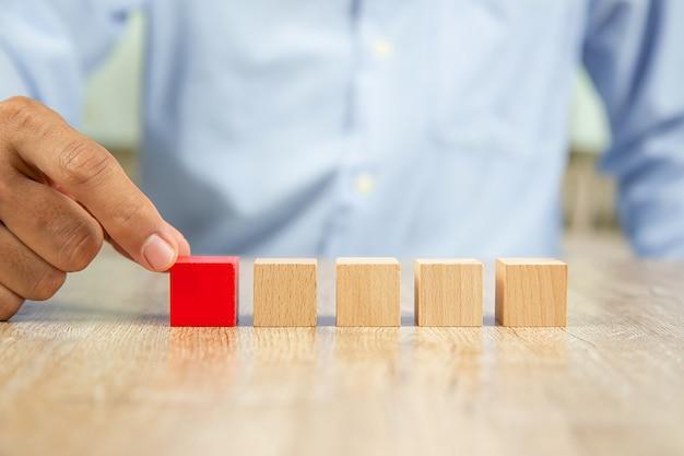 Geschäftsmannhand wählen rotes hölzernes blog ohne grafik. Premium Fotos