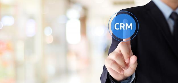 Geschäftsmannhandnote crm, kundenbeziehungs-management, ikone über unschärfehintergrund Premium Fotos