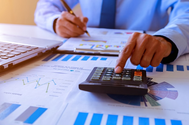 Geschäftsmannleute, die analysierend arbeiten und zusammenfassung berechnen Premium Fotos