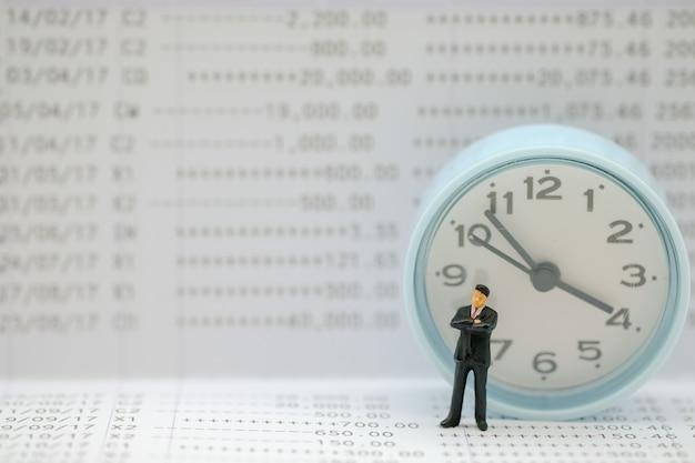 Geschäftsmannminiaturzahl, die auf banksparbuch mit runder uhr steht. Premium Fotos