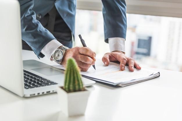 Geschäftsmannschreiben auf dokument mit stift auf schreibtisch mit laptop Kostenlose Fotos