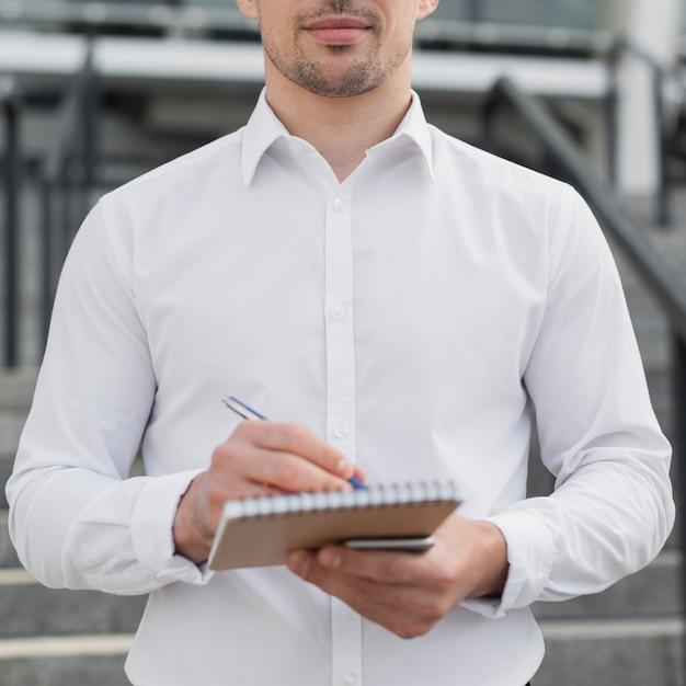 Geschäftsmannschreiben im notizblock Kostenlose Fotos