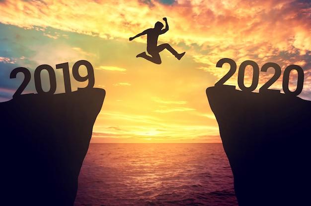 Geschäftsmannsprung zwischen 2019 und 2020 jahren. Premium Fotos
