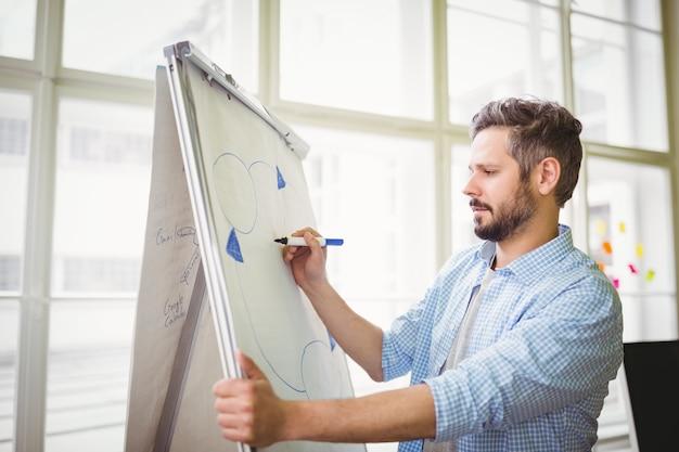 Geschäftsmannzeichnungsdiagramm auf whiteboard im kreativen büro Premium Fotos