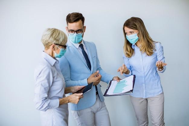Geschäftspartner, die im büro stehen und geschäftsergebnisse betrachten, während sie gesichtsmasken tragen, sind ein virenschutz Premium Fotos