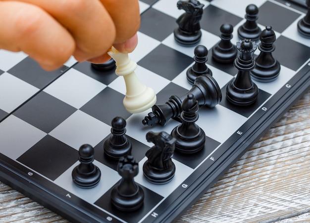Geschäftsstrategiekonzept auf hölzerner hintergrundhand, die schachfigur im wettbewerb bewegt. Kostenlose Fotos