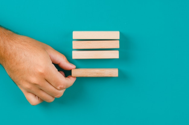 Geschäftsstrategiekonzept auf türkisfarbenem tisch flach legen. hand ziehen oder holzblock platzieren. Kostenlose Fotos