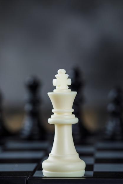 Geschäftsstrategiekonzept mit figuren auf schachbrett auf unscharfer und hölzerner tischnahaufnahme. Kostenlose Fotos