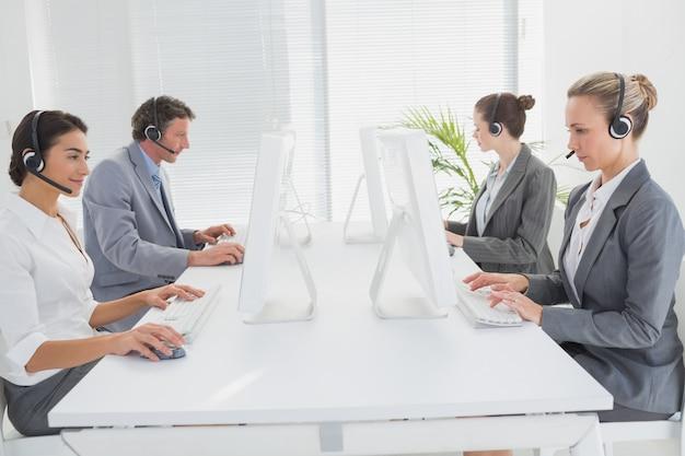 Geschäftsteam, das an computern arbeitet und kopfhörer trägt Premium Fotos