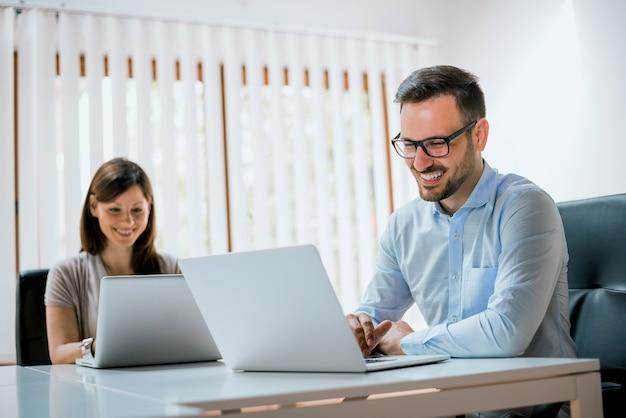 Geschäftsteam, das im büro auf laptop-computer arbeitet Premium Fotos