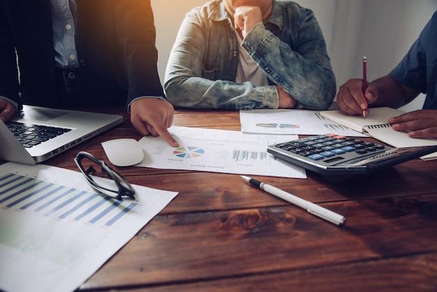 Geschäftsteam, das mit laptop und taschenrechner im büro des offenen raumes arbeitet. sitzungsbericht in bearbeitung Premium Fotos