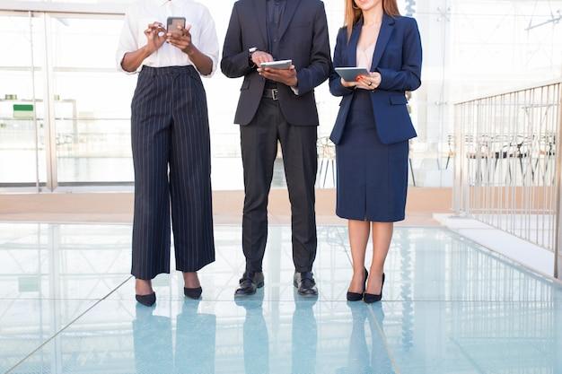 Geschäftsteam von drei unter verwendung der digitalen geräte in der bürohalle Kostenlose Fotos