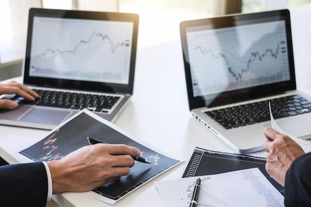 Geschäftsteaminvestition, die mit börsehandel des computer- und analysendiagramms arbeitet Premium Fotos