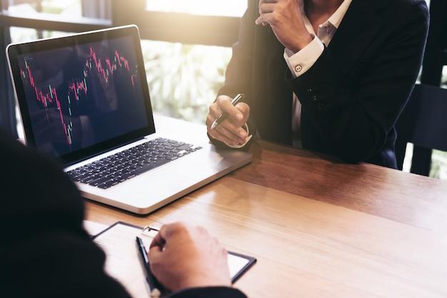 Geschäftsteaminvestition, die mit computer- und analysediagrammbörsenhandel arbeitet Premium Fotos