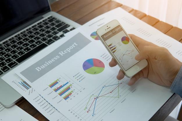 Geschäftsunterlagen auf bürotisch mit intelligentem telefon und diagramm finanziell Premium Fotos