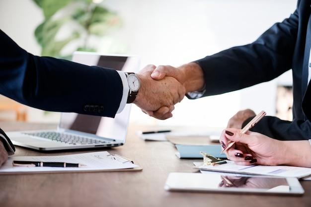 Geschäftsleute, die zusammen Hände rütteln Kostenlose Fotos
