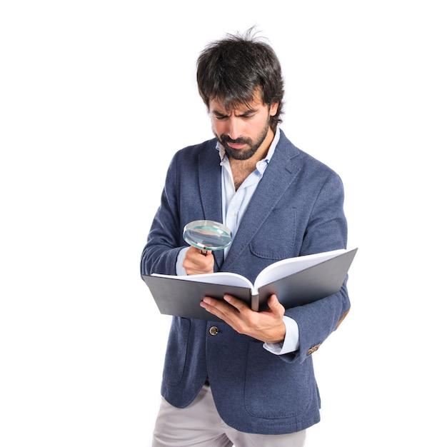 Geschäftsmann mit Lupe Reding ein Buch über weißem Hintergrund Kostenlose Fotos