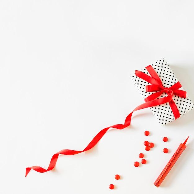 Geschenk gebunden mit rotem band nahe süßigkeiten und wunderkerze auf weißem hintergrund Kostenlose Fotos