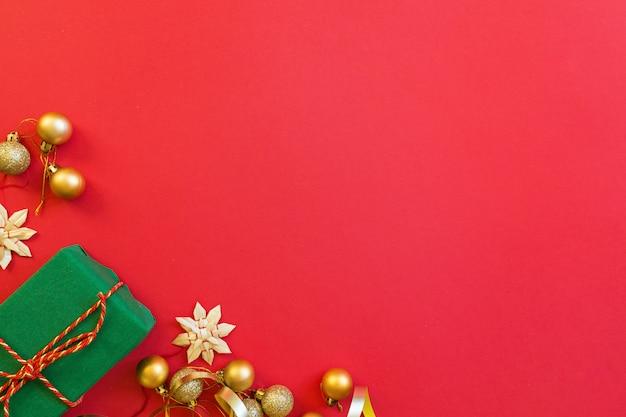 Geschenk, goldene spielwaren, die auf rotem hintergrund liegen Premium Fotos