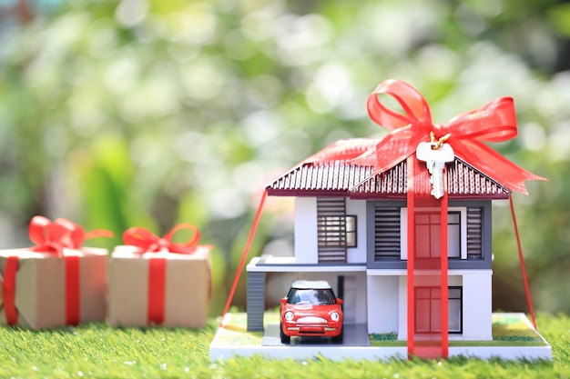 Geschenk neues zuhause und immobilien, musterhaus mit rotem band und das auto auf natürlichem grün Premium Fotos
