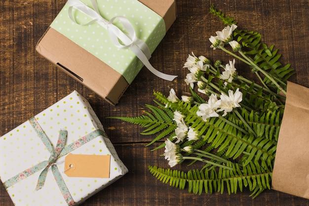 Geschenk verpackt mit blumen und blättern in der papiertüte über holztisch Kostenlose Fotos