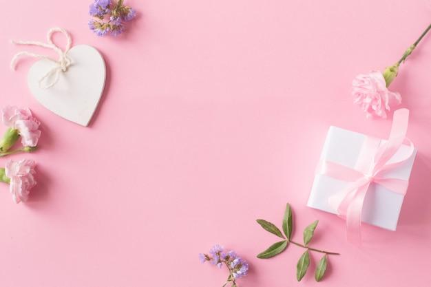 Geschenk, weißes hölzernes herz und blumen auf rosa hintergrund Premium Fotos