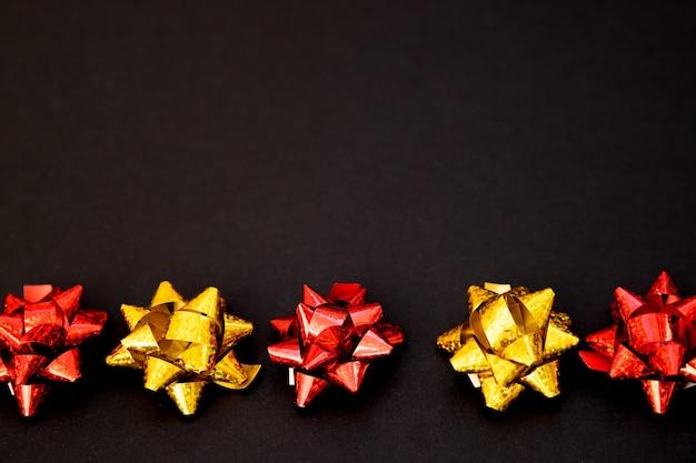 Geschenkbögen liegen in einer linie auf einem schwarzen hintergrund. weihnachten und neujahr. ein geburtstagsgeschenk. leerer platz für den text. stilfeiertagshintergrund. Premium Fotos