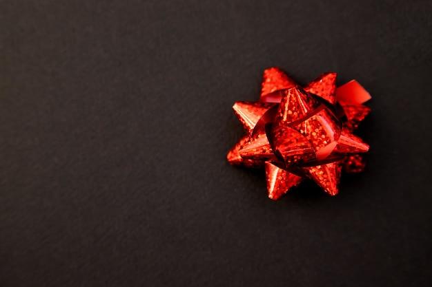 Geschenkbogen in rot auf schwarzem hintergrund. weihnachten und neujahr. ein geburtstagsgeschenk. leerer platz für den text. Premium Fotos