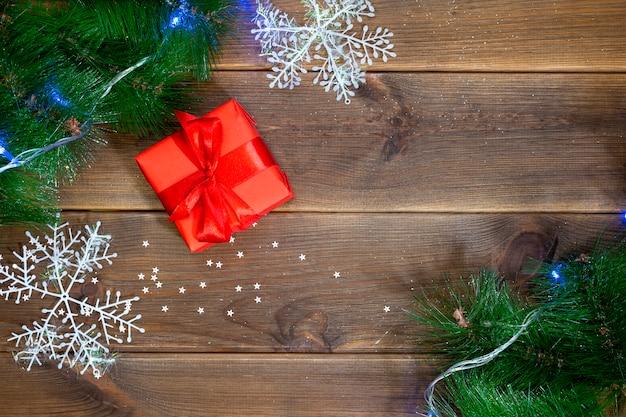 Geschenkbox auf einem holztisch, einer tabelle mit kiefernniederlassungen und roten bällen, konzept des neuen jahres Premium Fotos