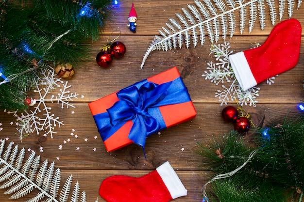 Geschenkbox auf einem holztisch, einer tabelle mit kiefernniederlassungen und roten bällen Premium Fotos